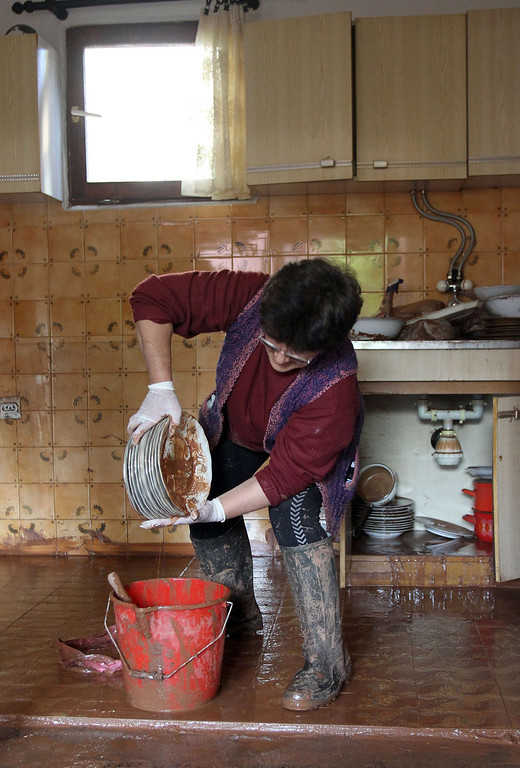 Description of . A woman washes plates after floods hit her house in the town of Svilajnac, 120 kilometers south of Belgrade, on May 20, 2014. The Balkans were on alert Tuesday as swollen rivers were due to reach new peaks after days of devastating floods and landslides that have claimed at least 49 lives.  AFP PHOTO / SASA DJORDJEVIC/AFP/Getty Images