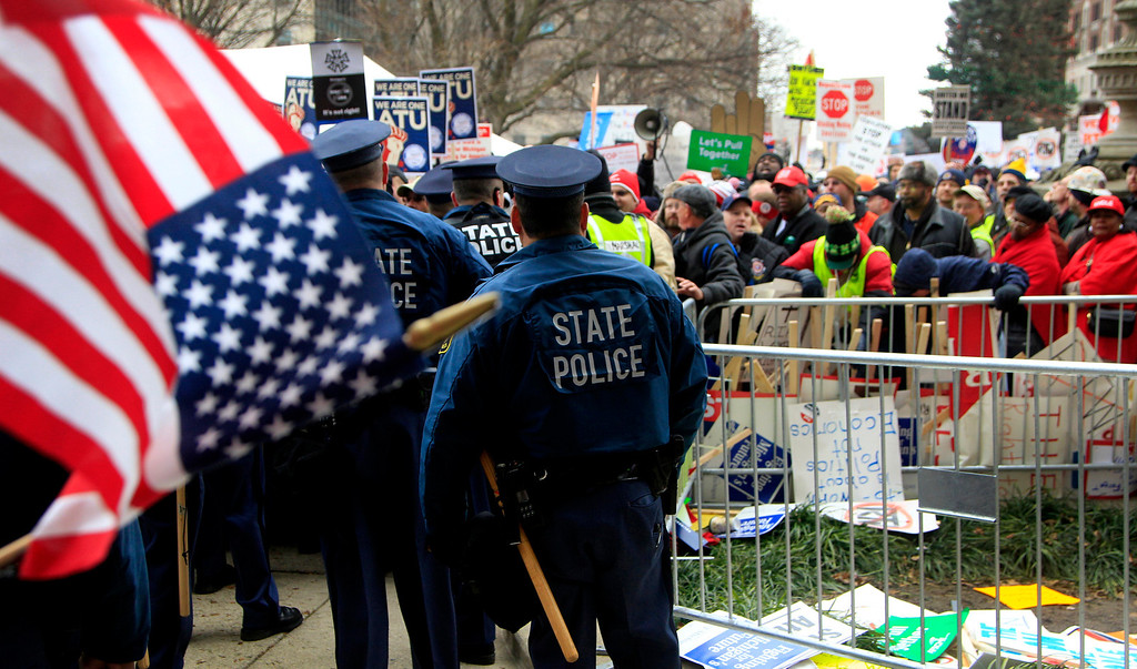 Description of . Michigan State Police stand guard at an entrance to the State Capitol in Lansing, Mich., Tuesday, Dec. 11, 2012. The crowd is protesting right-to-work legislation that was passed by the state legislature last week. (AP Photo/Carlos Osorio)