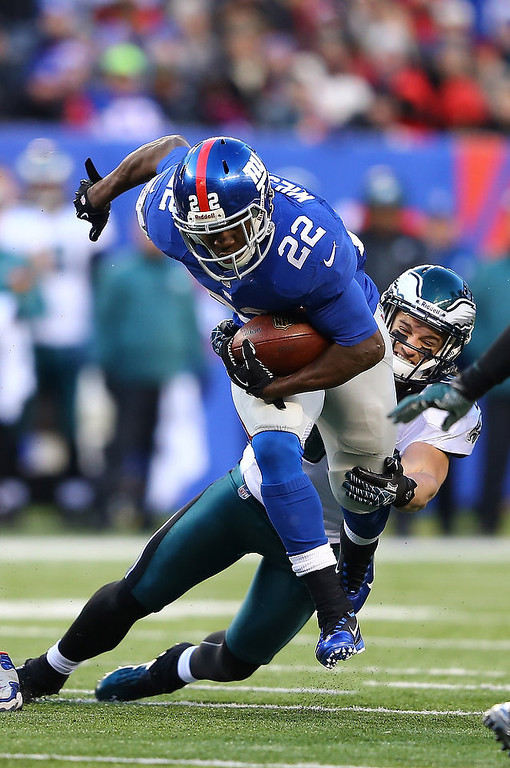 Description of . David Wilson #22 of the New York Giants runs as  Colt Anderson #30 of the Philadelphia Eagles defends during their game at MetLife Stadium on December 30, 2012 in East Rutherford, New Jersey.  (Photo by Al Bello/Getty Images)