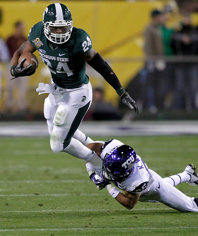 Description of . Michigan State running back Le'Veon Bell (24) is tripped up by TCU cornerback Kevin White (25) during the first half of the Buffalo Wild Wings Bowl NCAA college football game, Saturday, Dec. 29, 2012, in Tempe, Ariz. (AP Photo/Matt York)