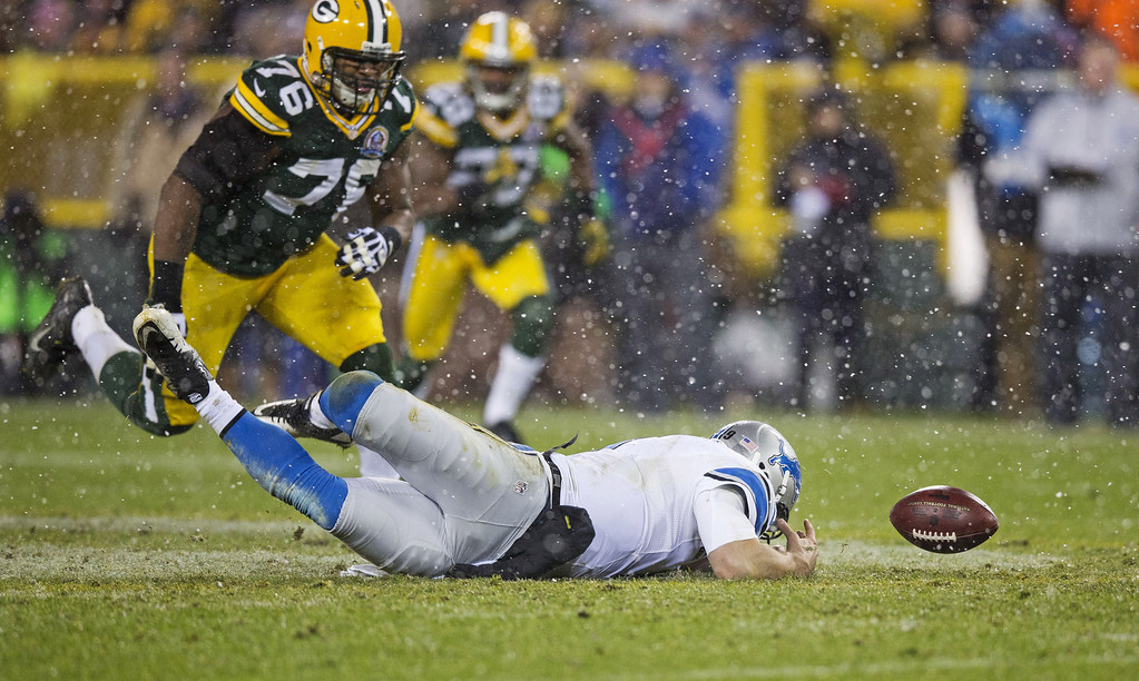 Description of . GREEN BAY, WI - DECEMBER 9:  Matthew Stafford #9 of the Detroit Lions dives for the ball he fumbled as Mike Daniels #76 of the Green Bay Packers closes in at Lambeau Field on December 9, 2012 in Green Bay, Wisconsin.  (Photo by Tom Lynn/Getty Images)