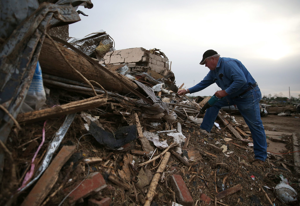 Description of . John Folked uses an electric saw to cut downed power lines where his Realty business once stood before a tornado destroyed it two days earlier, on April 29, 2014 in Vilonia, Arkansas.  (Photo by Mark Wilson/Getty Images)