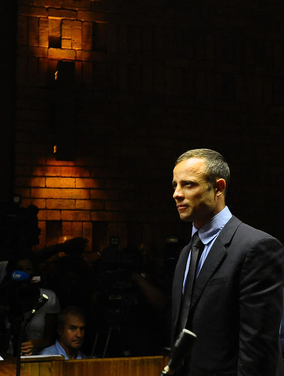 Description of . Olympic athlete Oscar Pistorius stands in court following his bail hearing in Pretoria, South Africa, Tuesday, Feb. 19, 2013.  Pistorius fired into the door of a small bathroom where his girlfriend was cowering after a shouting match on Valentine's Day, hitting her three times, a South African prosecutor said Tuesday as he accused the sports icon of premeditated murder.  The magistrate ruled that Pistorius faces the harshest bail requirements available in South African law, but did not elaborate before a break was called in the session. (AP Photo)