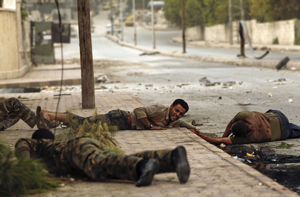 Description of . Members of the Al-Baraa bin Malek batallion, part of the Free Syria Army's Al-Fatah brigade, duck to the ground as they pull a man (R) who was shot by a sniper twice in the Bustan al-Basha district of the northern city of Aleppo on October 20, 2012. Due to the risk of being shot by the sniper, no one was able to rescue the man who eventually ran towards rebels, only to be shot by the sniper a second time. Rebels then pulled him and rushed him to a hospital, though it is not known if he survived. Three civilians were shot on this main road in the space of three hours by the same sniper. (Javier Manzano/AFP/Getty Images)