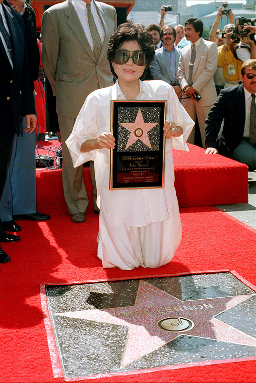 Description of . Yoko Ono, wife of late Beatle John Lennon, poses in front of a star honoring Lennon after it is unveiled on the Hollywood Walk of Fame in Los Angeles, Ca., on Sept. 30, 1988.  (AP Photo/Alan Greth)