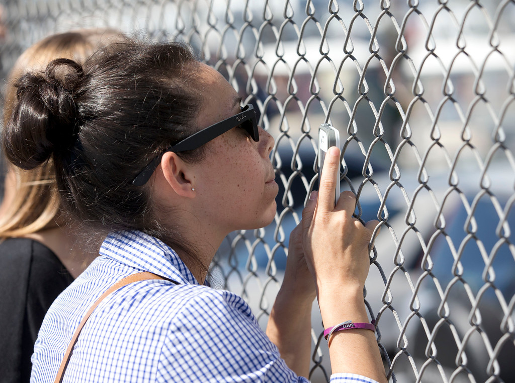 . Ana Gull, 23, of Doral, Fla., stands outside the Turner Guilford Knight Correctional Center, during her lunch hours to see if she could get a glimpse of pop singer Justin Bieber, Thursday Jan. 23, 2014 in Doral, Fla. Bieber was arrested and charged with driving under the influence and resisting arrest after police said they saw him speeding down a residential street in Miami Beach in a yellow Lamborghini earlier in the day.  (AP Photo/Wilfredo Lee)