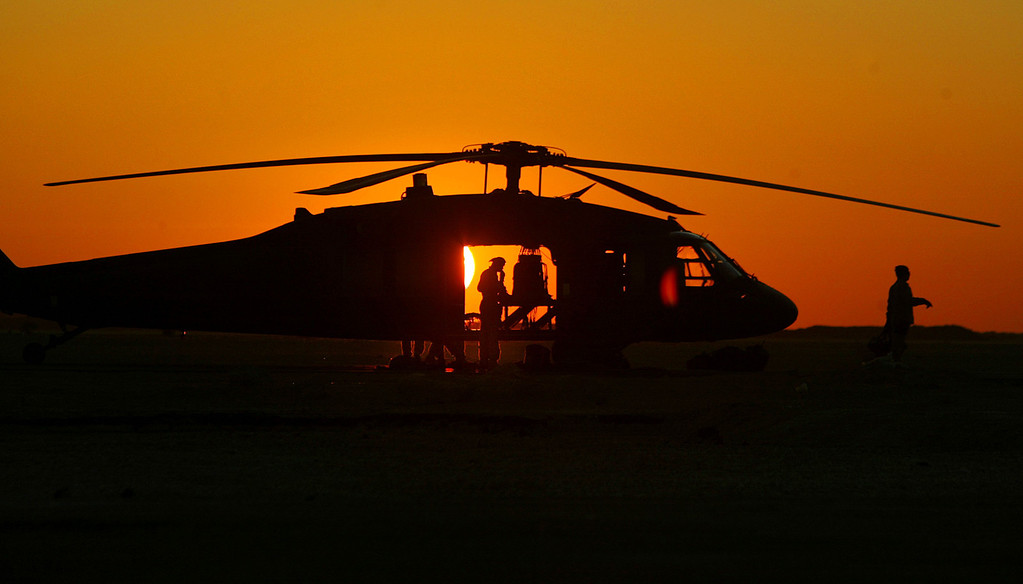 Description of . A U.S. Army Black Hawk helicopter crew works on a runway prior to flying in the violent so-called Sunni Triangle area January 19, 2004 at Forward Operating Base Ridgway, Iraq. The helicopter\'s crew was one of many from the 2nd Battalion, 82nd Aviation Brigade of the 82nd Airborne Division based at Forward Operating Base Ridgway located near the restive town of Fallujah. (Photo by Mario Tama/Getty Images)