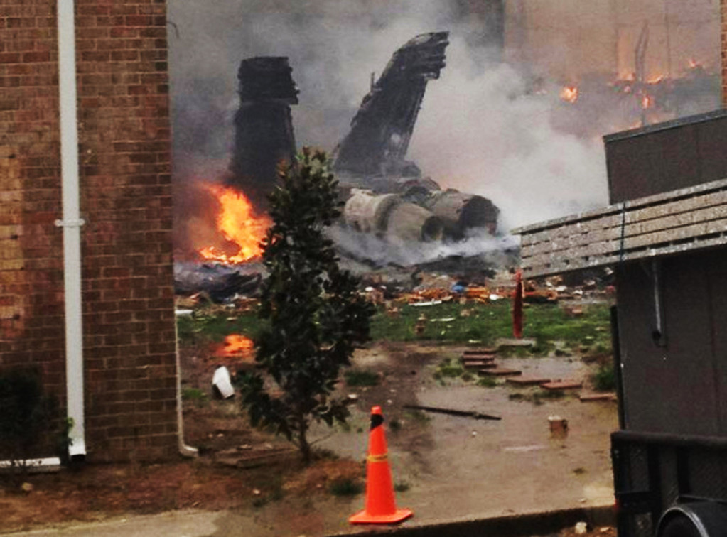 Description of . In this April 6, 2012 file photo, the burning fuselage of an F/A-18 Hornet lies smoldering after crashing into a residential building in Virginia Beach, Va.  (AP Photo/Zach Zapatero, File)