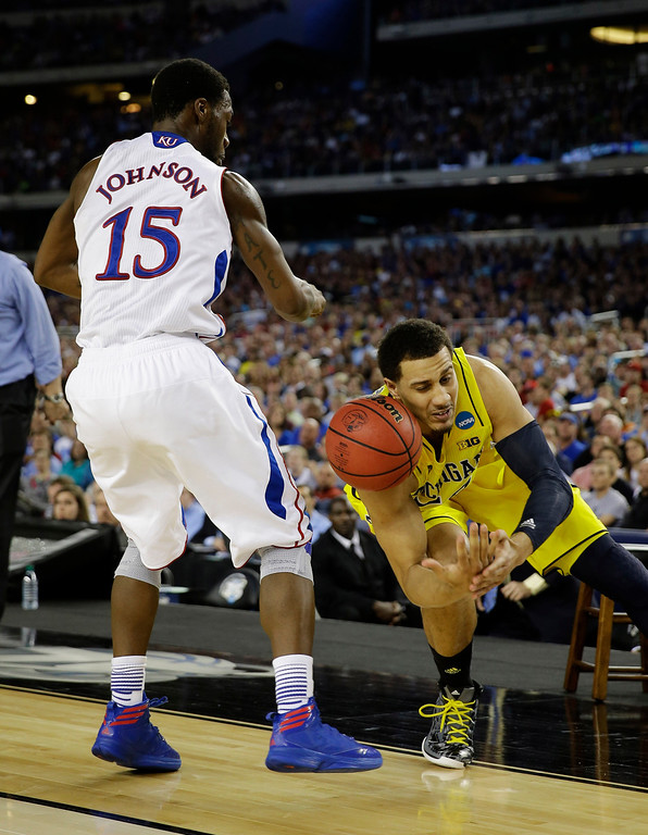 Description of . Kansas\' Elijah Johnson (15) strips the ball from Michigan\'s Jordan Morgan during the second half of a regional semifinal game in the NCAA college basketball tournament, Friday, March 29, 2013, in Arlington, Texas. (AP Photo/David J. Phillip)