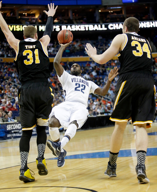 Description of . Villanova's JayVaughn Pinkston (22) shoots over Milwaukee's Matt Tiby (31) and Austin Arians (34) during the first half of a second-round game in the NCAA college basketball tournament in Buffalo, N.Y., Thursday, March 20, 2014. (AP Photo/Nick LoVerde)