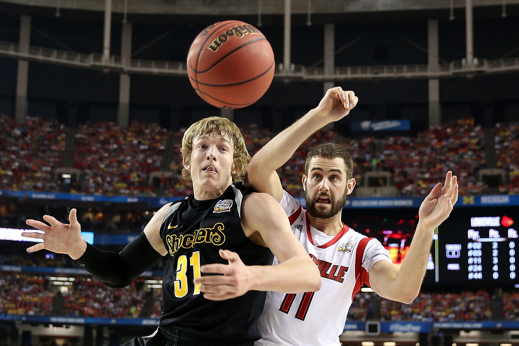 Description of . ATLANTA, GA - APRIL 06:  Ron Baker #31 of the Wichita State Shockers fights for a rebound in the first half against Luke Hancock #11 of the Louisville Cardinals during the 2013 NCAA Men's Final Four Semifinal at the Georgia Dome on April 6, 2013 in Atlanta, Georgia.  (Photo by Andy Lyons/Getty Images)