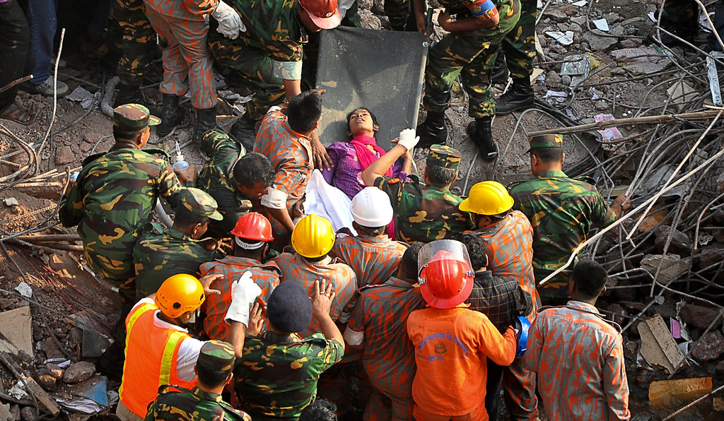 Description of . A survivor lies on a stretcher after being pulled out from the rubble of a building that collapsed in Savar, near Dhaka, Bangladesh, Friday, May 10, 2013. Rescue workers in Bangladesh freed the woman buried for 17 days inside the wreckage of a garment factory building that collapsed, killing more than 1,000 people. Soldiers at the site said her name was Reshma and described her as being in remarkably good shape despite her ordeal. (AP Photo)