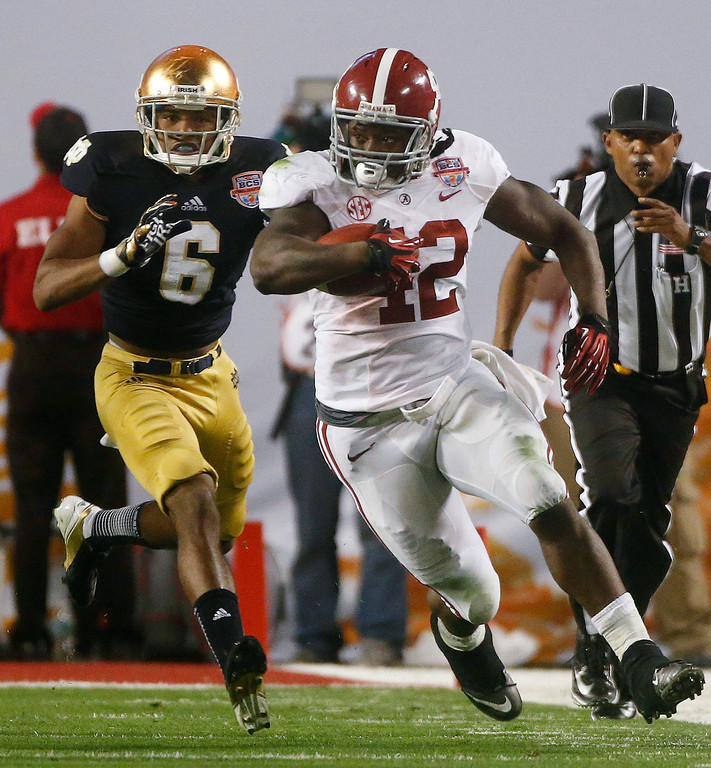 Description of . Alabama's Eddie Lacy (42) runs past Notre Dame cornerback KeiVarae Russell during the second half of the BCS National Championship college football game Monday, Jan. 7, 2013, in Miami. (AP Photo/John Bazemore)