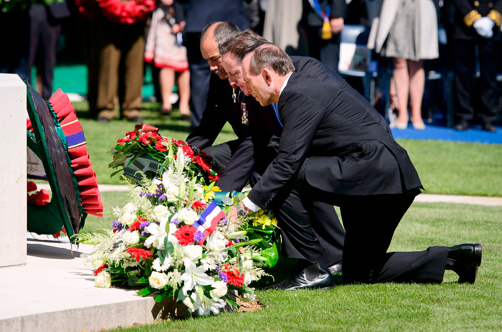 Description of . New Zealand's Prime Minister John Key, left, British Prime Minister David Cameron, center, and Australia's Prime Minister Tony Abbott, right, lay wreaths during a British D-Day commemoration ceremony at the Bayeux cemetery, northern France, Friday, June 6, 2014. World leaders and veterans gathered by the beaches of Normandy on Friday to mark the 70th anniversary of World War Two's D-Day landings. (AP Photo/Leon Neal, Pool)