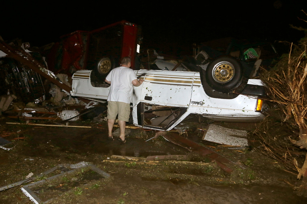 Description of . John Ward, an automobile and RV dealer, looks at tornado damage to one of his trucks in Mayflower, Ark., Sunday, April 27, 2014. At least 16 people died Sunday night in Arkansas as a tornado carved an 80-mile path of destruction. (AP Photo/Danny Johnston)
