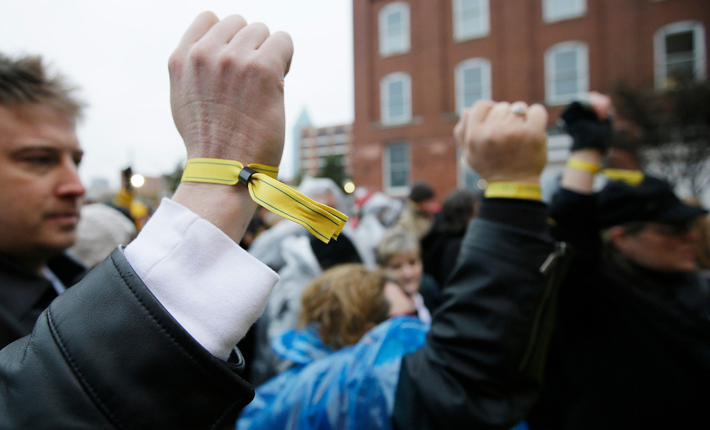 Description of . Sean MacLean of Calgary, Alberta, Canada, left, and Colleen Bonner of Hurst, Texas display yellow wrist bands for access before ceremony to mark the 50th anniversary of the assassination of John F. Kennedy, Friday, Nov. 22, 2013, at Dealey Plaza in Dallas. President Kennedy's motorcade was passing through Dealey Plaza when shots rang out on Nov. 22, 1963. (AP Photo/Tony Gutierrez)