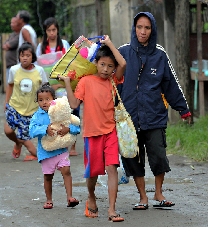 Description of . Residents evacuate to safer grounds in anticipation of Typhoon Bopha in Butuan city in southeastern Philippines Tuesday, Dec. 4, 2012. Typhoon Bopha, one of the strongest typhoons to hit the Philippines this year, barreled across the country's south on Tuesday, killing dozens of people and forcing more than 50,000 to flee from inundated villages. (AP Photo/Erwin Mascarinas)
