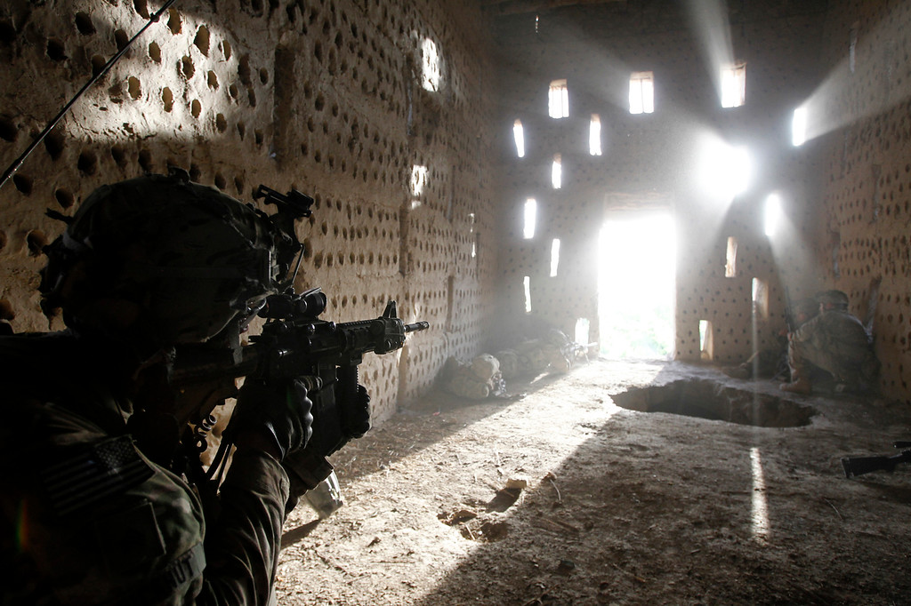 Description of . U.S. soldier Nicholas Dickhut from 5-20 infantry Regiment attached to 82nd Airborne points his rifle at a doorway after coming under fire by the Taliban while on patrol in Zharay district in Kandahar province, southern Afghanistan April 26, 2012. REUTERS/Baz Ratner