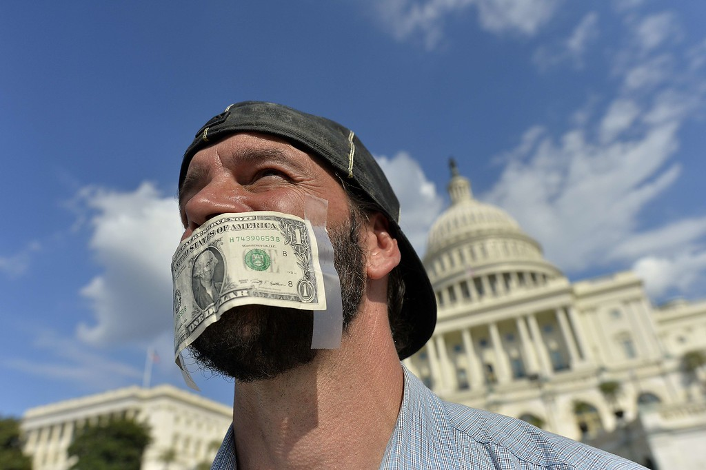 Description of . A protester covers his mouth with a dollar bill as he joins other in front of the US Capitol in Washington, DC, on October 1, 2013 urging congress to pass the budget bill. US President Obama slammed Republicans for shutting down the government as part of an