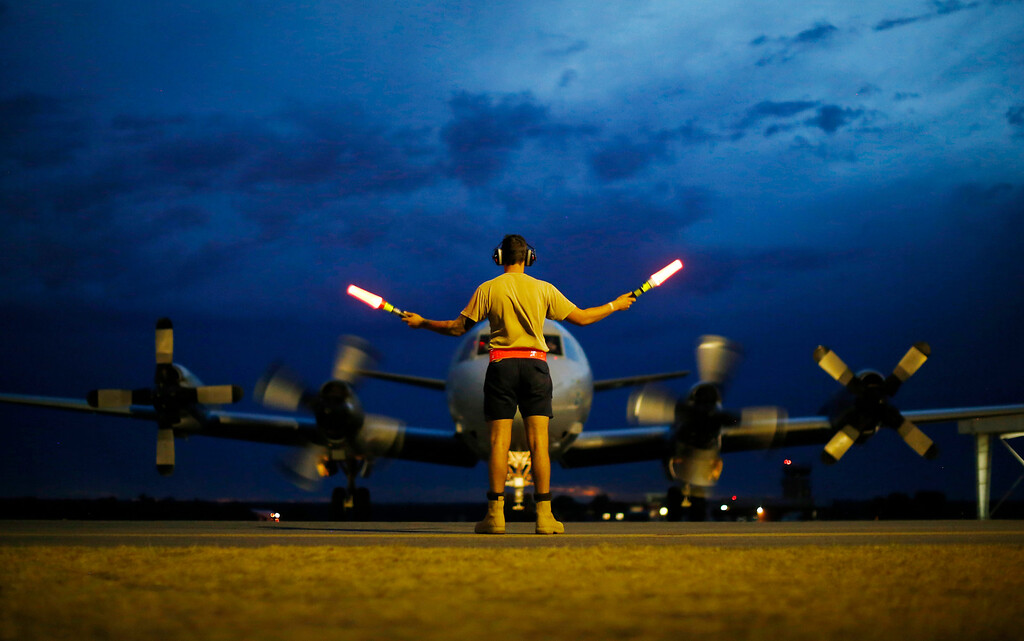 Description of . A ground controller guides a Royal Australian Air Force AP-3C Orion to rest after sunset upon its return from a search for the missing Malaysia Airlines flight MH370 over the Indian Ocean, at the Royal Australian Air Force base Pearce in Perth, Monday, March 24, 2014. (AP Photo/Jason Reed, Pool)