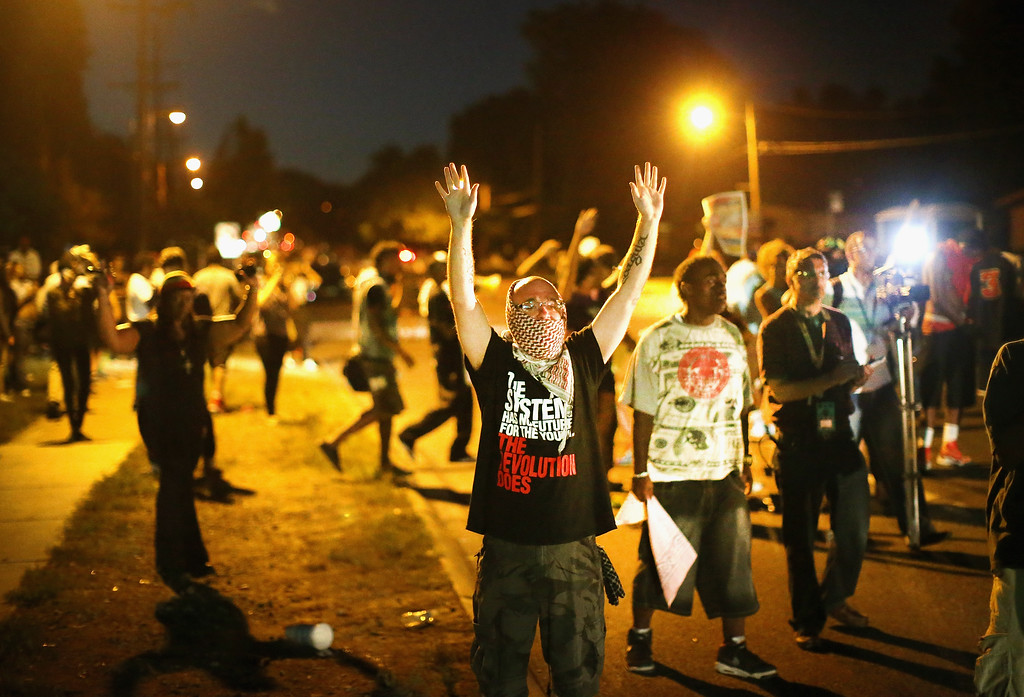 Description of . Demonstrators protest the shooting death of teenager Michael Brown on August 13, 2014 in Ferguson, Missouri. Brown was shot and killed by a Ferguson police officer on Saturday. Ferguson, a St. Louis suburb, is experiencing its fourth day of violent protests since the killing.  (Photo by Scott Olson/Getty Images)