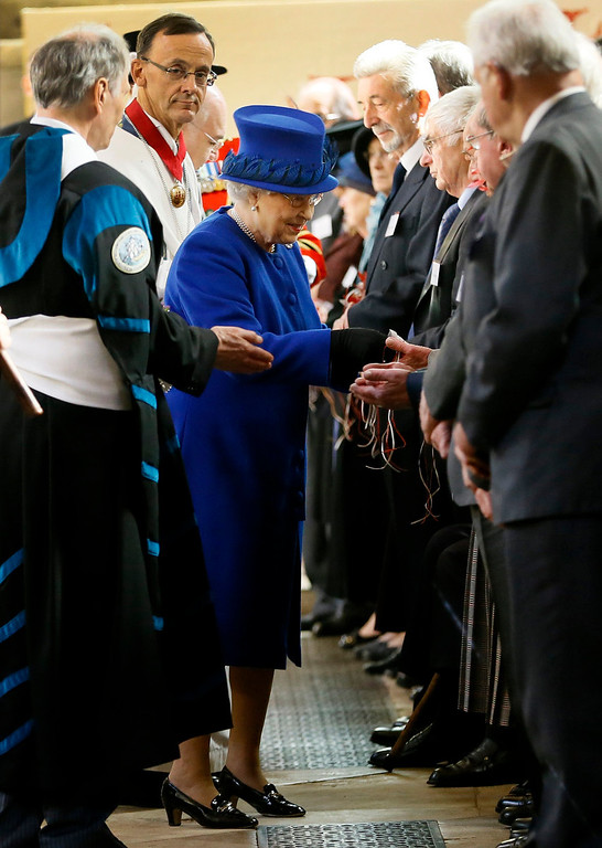 Description of . Britain's Queen Elizabeth II, centre, distributes Maundy money during the Maundy service,  at Christ Church Cathedral in Oxford, England,  Thursday, March 28, 2013. The Queen distributed the Maundy money to 87 women and 87 men, one for each of The Queenís 87 years. Each recipient receives two purses, one red and one white. The red purse will contain a 5 pound coin and 50 pence coin commemorating the 60th anniversary of The Queenís Coronation. The white purse will contain uniquely minted Maundy Money. This takes the form of silver one, two, three and four penny pieces, the sum of which equals the number of years the Monarch has years of age. This year there will be 87 pennies worth distributed. (AP Photo/Kirsty Wigglesworth, Pool)