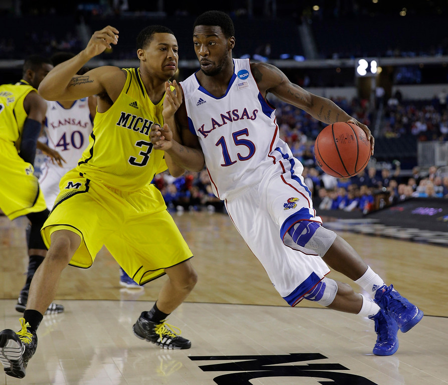 Description of . Kansas\' Elijah Johnson (15) tries to drive past Michigan\'s Trey Burke during the first half of a regional semifinal game in the NCAA college basketball tournament, Friday, March 29, 2013, in Arlington, Texas. (AP Photo/David J. Phillip)