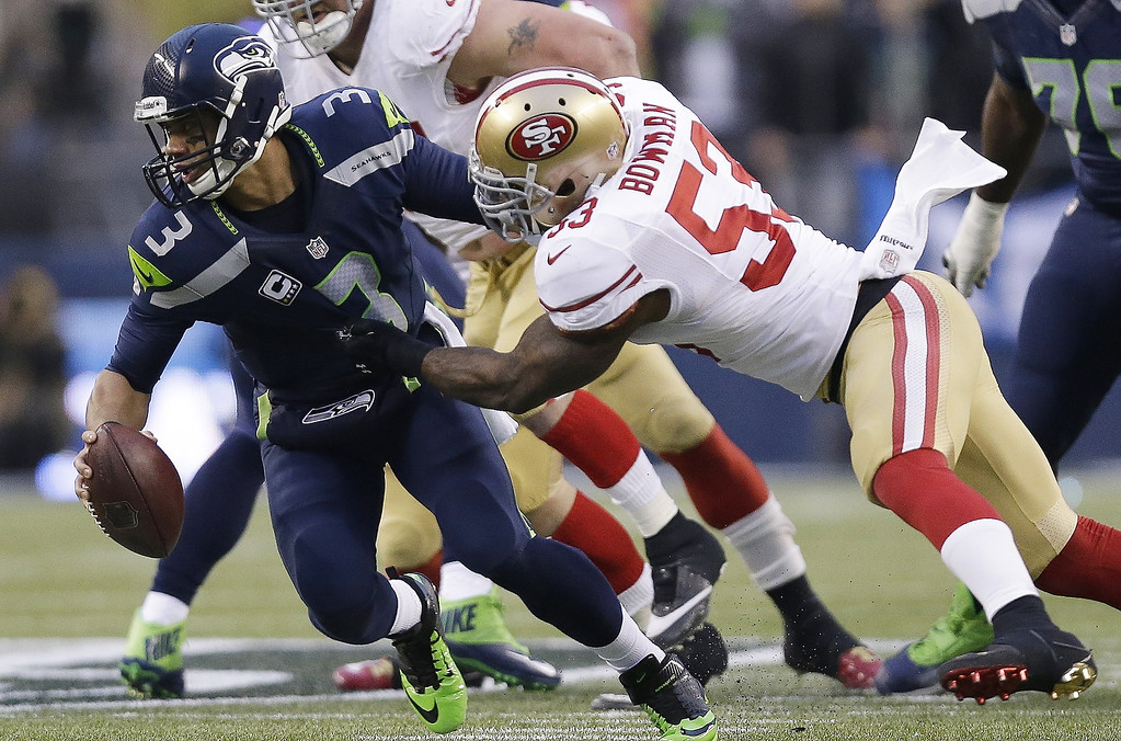 . Seattle Seahawks\' Russell Wilson is sacked by San Francisco 49ers\' NaVorro Bowman (53) during the first half of the NFL football NFC Championship game Sunday, Jan. 19, 2014, in Seattle. (AP Photo/Marcio Jose Sanchez)
