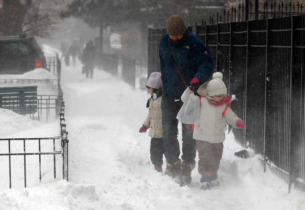 Description of . Commuters walk against blowing snow Wednesday, Feb. 5, 2014, in Chicago. Heavy, blowing snow is moving across much of Illinois as the state gets pelted by the latest round of winter weather. (AP Photo/Kiichiro Sato)