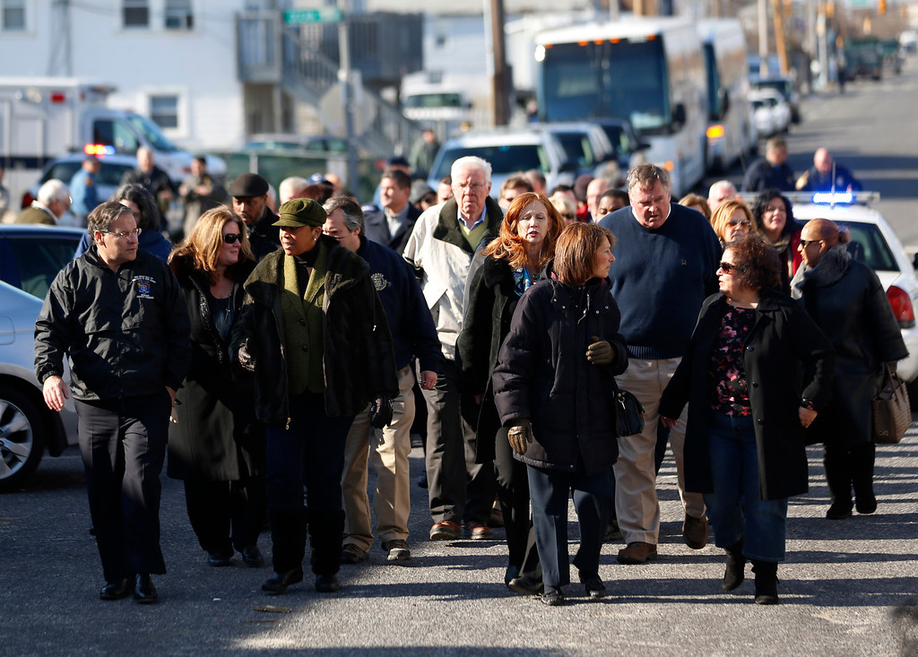 Description of . Members of the New Jersey General Assembly walk toward the Seaside Heights boardwalk to look at the damage caused by Superstorm Sandy during a tour of the New Jersey Shore, Thursday, Nov. 29, 2012, in Seaside Heights, N.J. (AP Photo/Julio Cortez)