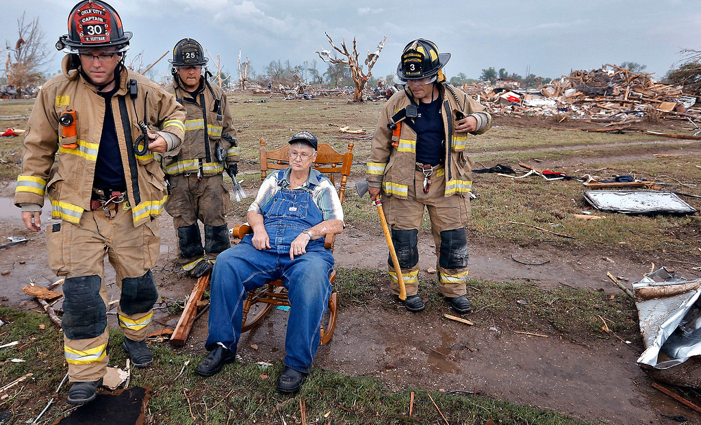 . Oklahoma City fire fighters check on the status of Gene Tripp as he sits in his rocking chair where his home once stood after being destroyed by a tornado hit the area near 149th and Drexel on Monday, May 20, 2013 in Oklahoma City, Okla.  (AP Photo/The Oklahoman, Chris Landsberger)