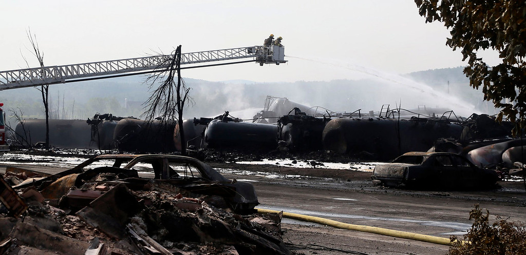 Description of . Firefighters work at the scene of a train derailment in Lac Megantic, Quebec, July 7, 2013.  A driverless freight train carrying tankers of petroleum products derailed at high speed and exploded into a giant fireball in the middle of the small Canadian town of Lac-Megantic early on Saturday, destroying dozens of buildings and leaving an unknown number of people feared missing.  REUTERS/Christinne Muschi