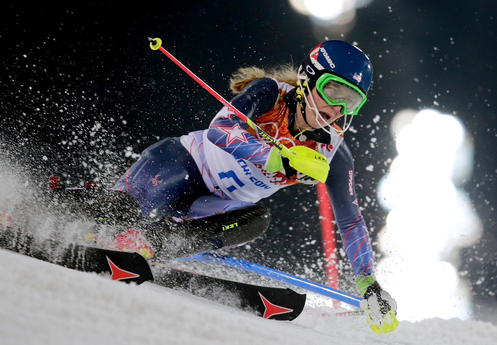 Description of . Gold medal winner Mikaela Shiffrin skis past a gate in the women's slalom at the Sochi 2014 Winter Olympics, Friday, Feb. 21, 2014, in Krasnaya Polyana, Russia. (AP Photo/Charles Krupa)