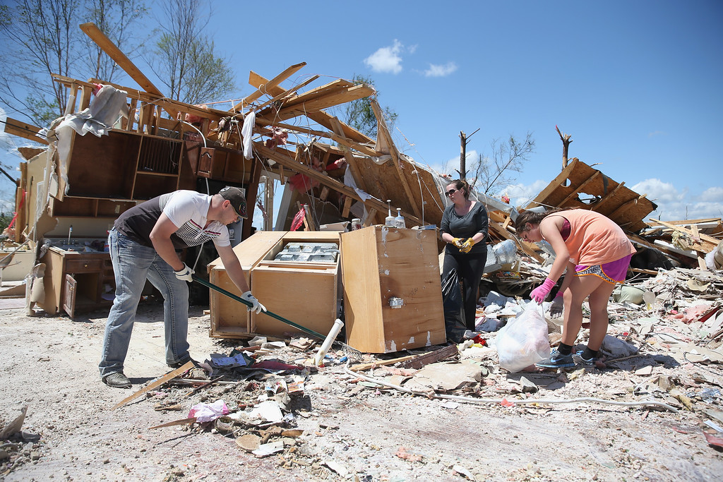 Description of . Ryan Smyth, Marla Jackson and Marion Ming (L-R) salvage what they can from the area that was the kitchen in a relative's home after it was destroyed on Monday by a tornado on April 30, 2014 in Louisville, Mississippi. Deadly tornadoes ripped through the region starting on April 27 leaving more than two dozen dead. The storm system has also brought severe flooding to Florida's Panhandle.  (Photo by Joe Raedle/Getty Images)