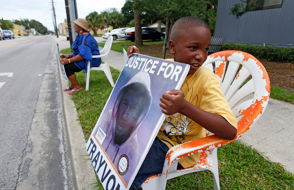 Description of . Antonio McVay, 8, holds a sign in front of his home in the Goldsboro Historical neighborhood, Saturday, July 13, 2013, in Sanford, Fla., while residents wait for word on the verdict in the George Zimmerman trial. Zimmerman has been charged with the 2012 shooting death of Trayvon Martin. (AP Photo/Mike Brown)