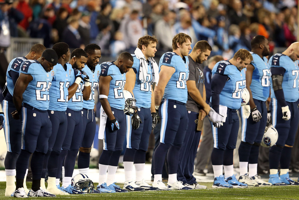 Description of . NASHVILLE, TN - DECEMBER 17:  The Tennessee Titans stand on the sideline for a moment in silence for the victims of the mass shooting that took place at Sandy Hook elementary school in Newtown, Connecticut prior to the game against the New York Jets at LP Field on December 17, 2012 in Nashville, Tennessee.  (Photo by Andy Lyons/Getty Images)