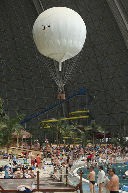 "Description of . Visitors lounge at the ""South Sea\"" beach as a hot air balloon passes overhead at the Tropical Islands indoor resort on February 15, 2013 in Krausnick, Germany. Located on the site of a former Soviet military air base, the resort occupies a hangar built originally to house airships designed to haul long-distance cargo. Tropical Islands opened to the public in 2004 and offers visitors a tropical getaway complete with exotic flora and fauna, a beach, lagoon, restaurants, water slide, evening shows, sauna, adventure park and overnights stays ranging from rudimentary to luxury. The hangar, which is 360 metres long, 210 metres wide and 107 metres high, is tall enough to enclose the Statue of Liberty.  (Photo by Sean Gallup/Getty Images)"