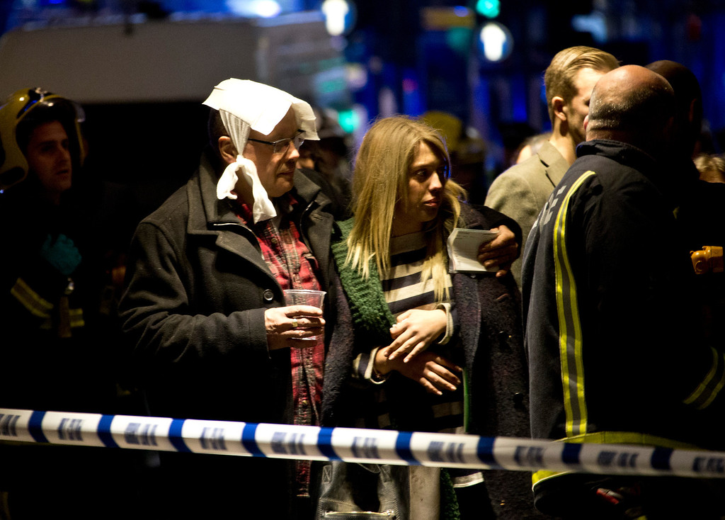""". A  bandaged man comforts a woman  following an incident at the Apollo Theatre, in London\'s Shaftesbury Avenue, Thursday evening, Dec. 19, 2013, during a performance , with police saying there were \""""a number\"""" of casualties. (AP Photo by Joel Ryan, Invision)"""