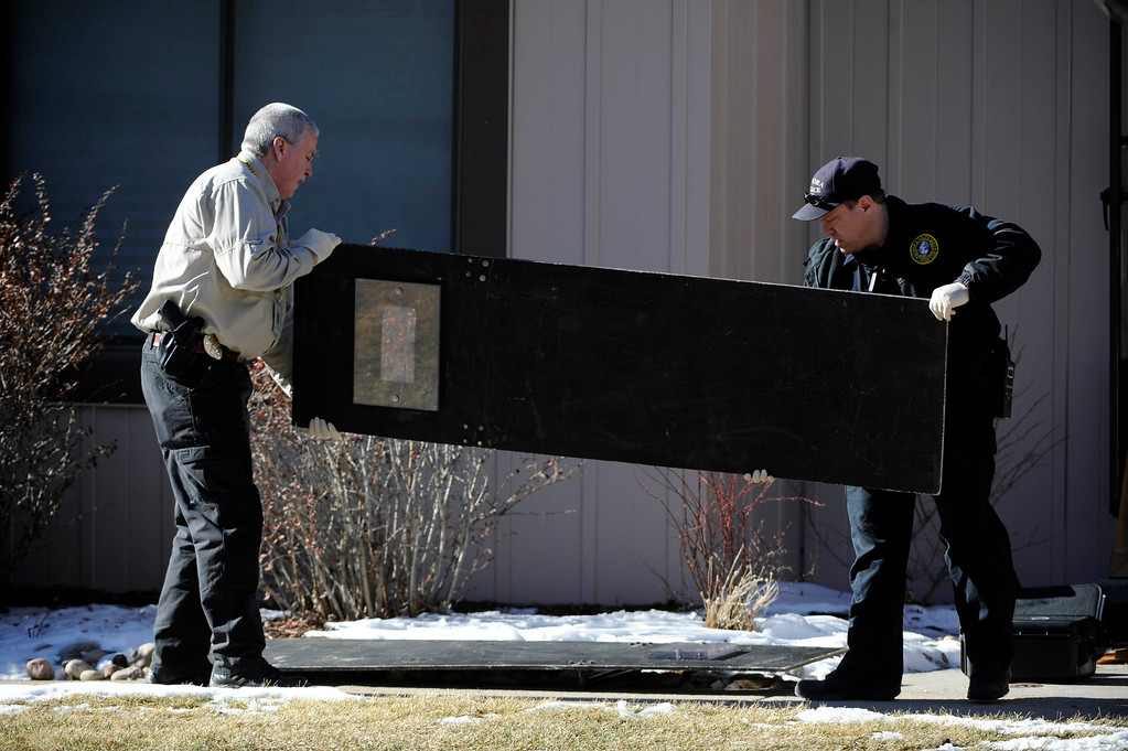 Description of . Aurora Police investigators take a shield out of a town home next to 16005c  Ithaca Place in Aurora Saturday afternoon. The bodies of four people, including a gunman are dead at the scene following a standoff situation early Saturday morning. The Denver Post/ Andy Cross
