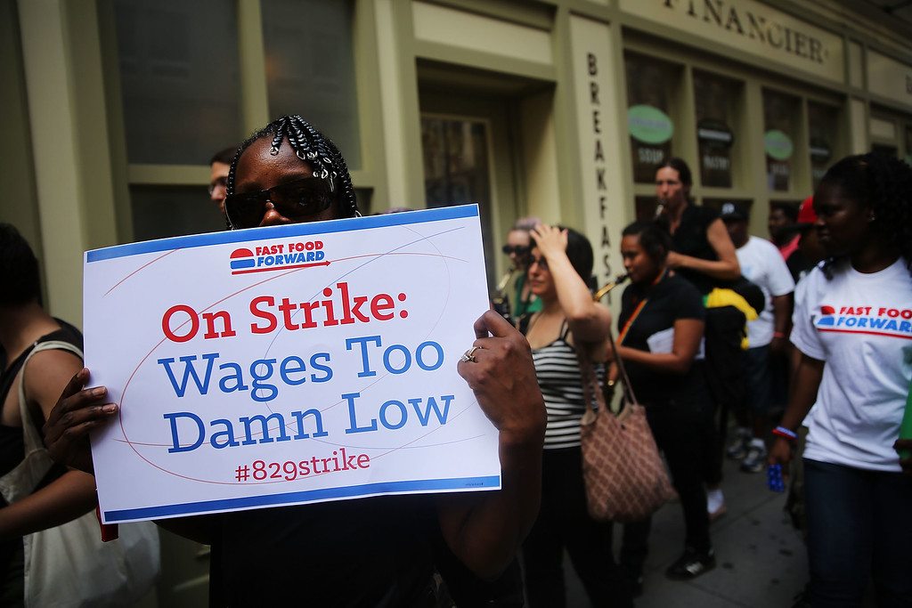 Description of . Employees and supporters demonstrate outside of a Wendy's and Burger King fast-food restaurants to demand higher pay and the right to form a union on August 29, 2013 in New York City.   (Photo by Spencer Platt/Getty Images)