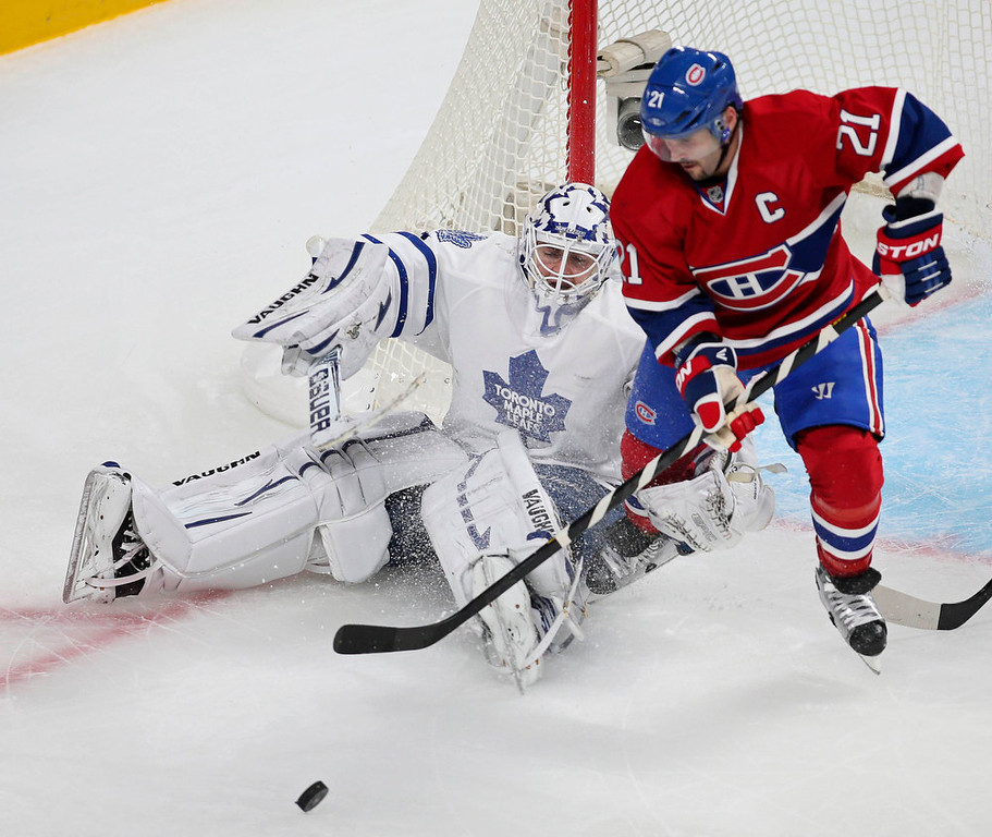 Description of . Toronto Maple Leafs goaltender Ben Scrivens (L) makes a save against Montreal Canadiens' Brian Gionta (21) during the first period of their NHL hockey game in Montreal January 19, 2013.  REUTERS/Christinne Muschi