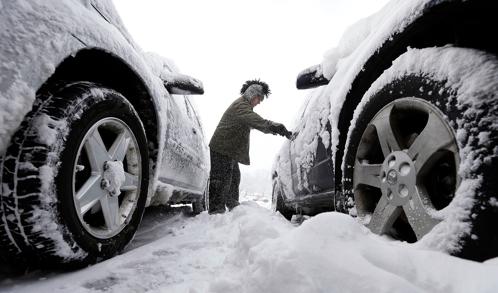 Description of . Noah Nichols, of Des Moines, Iowa, cleans snow off his car, Thursday, Dec. 20, 2012, in Des Moines, Iowa. The first widespread snowstorm of the season began a slow crawl across the Midwest on Thursday with some areas receiving as much as 15 inches of snow. (AP Photo/Charlie Neibergall)