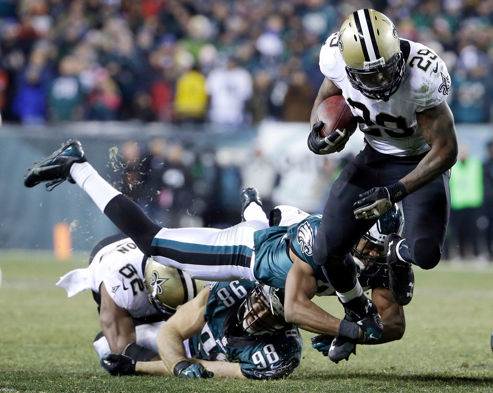 Description of . New Orleans Saints' Khiry Robinson, right, tries to get past a diving Philadelphia Eagles' Bradley Fletcher during the second half of an NFL wild-card playoff football game, Saturday, Jan. 4, 2014, in Philadelphia. (AP Photo/Matt Rourke)