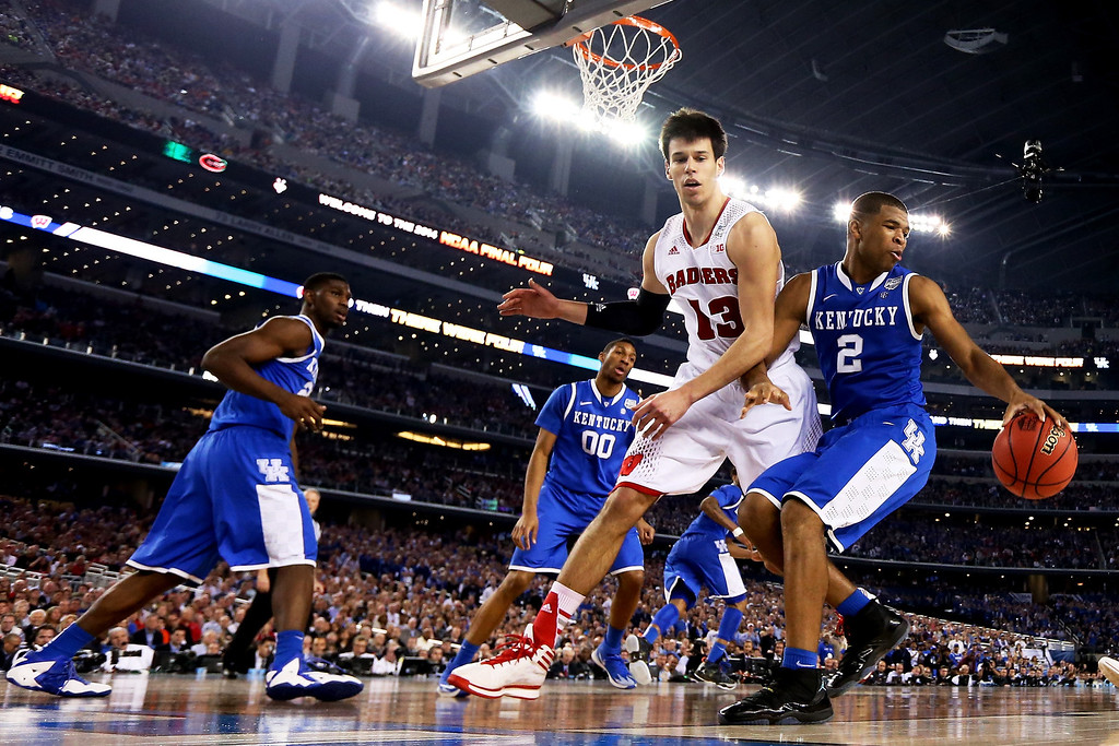 Description of . ARLINGTON, TX - APRIL 05: Aaron Harrison #2 of the Kentucky Wildcats drives to the basket as Duje Dukan #13 of the Wisconsin Badgers defends during the NCAA Men's Final Four Semifinal at AT&T Stadium on April 5, 2014 in Arlington, Texas.  (Photo by Tom Pennington/Getty Images)