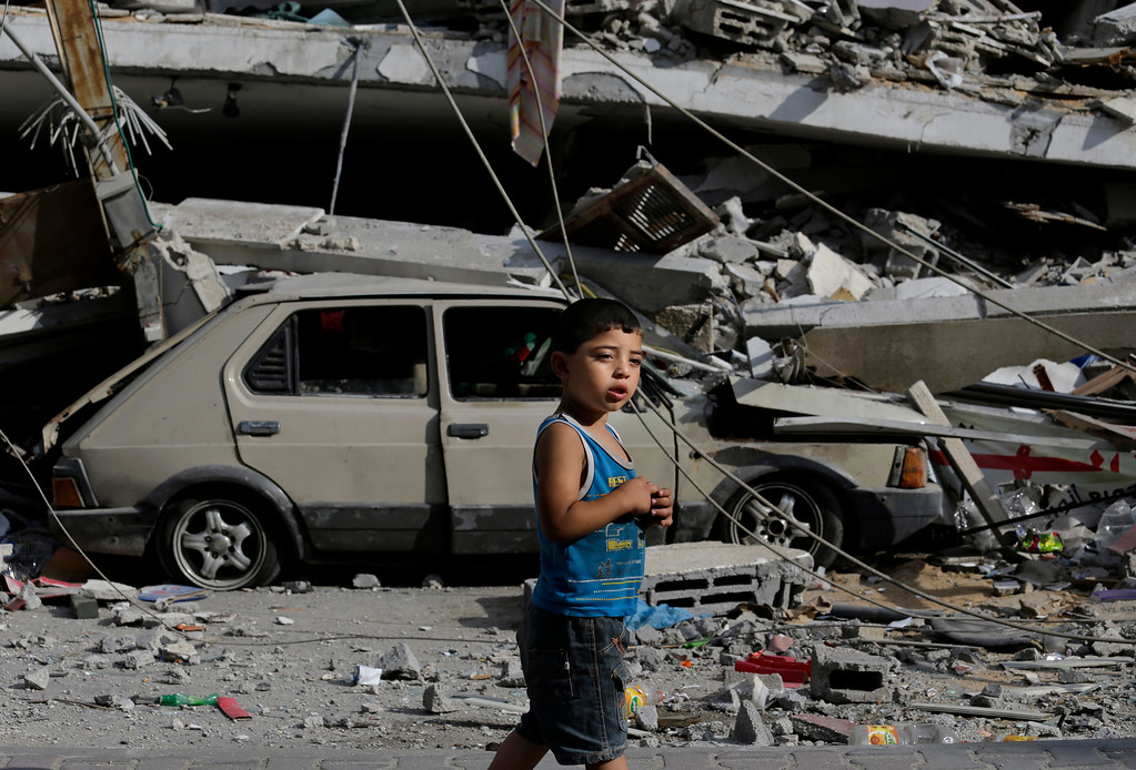 Description of . Palestinian Abdel Aziz Jendiyah, 4, walks past a six-story building, destroyed by an Israeli strike earlier during the war, adjacent to his family house, in the Sabra neighborhood of Gaza City, northern Gaza Strip, Thursday, July 31, 2014. The Jendiyah family building houses 21 members of the extended family, and now with several rooms destroyed, they try to go about their lives, without electricity and without running water for several hours a day. (AP Photo/Lefteris Pitarakis)