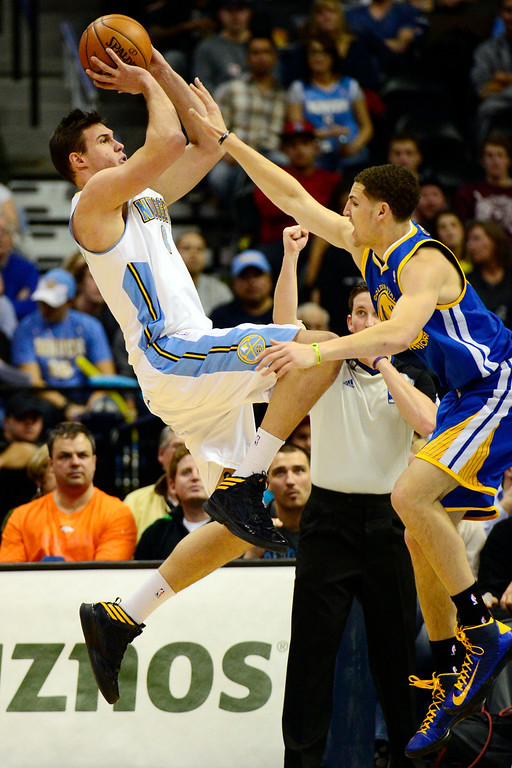 Description of . Golden State Warriors shooting guard Klay Thompson (11) defends Denver Nuggets small forward Danilo Gallinari (8) during the second half of the Nuggets' 116-105 win at the Pepsi Center on Sunday, January 13, 2013. AAron Ontiveroz, The Denver Post