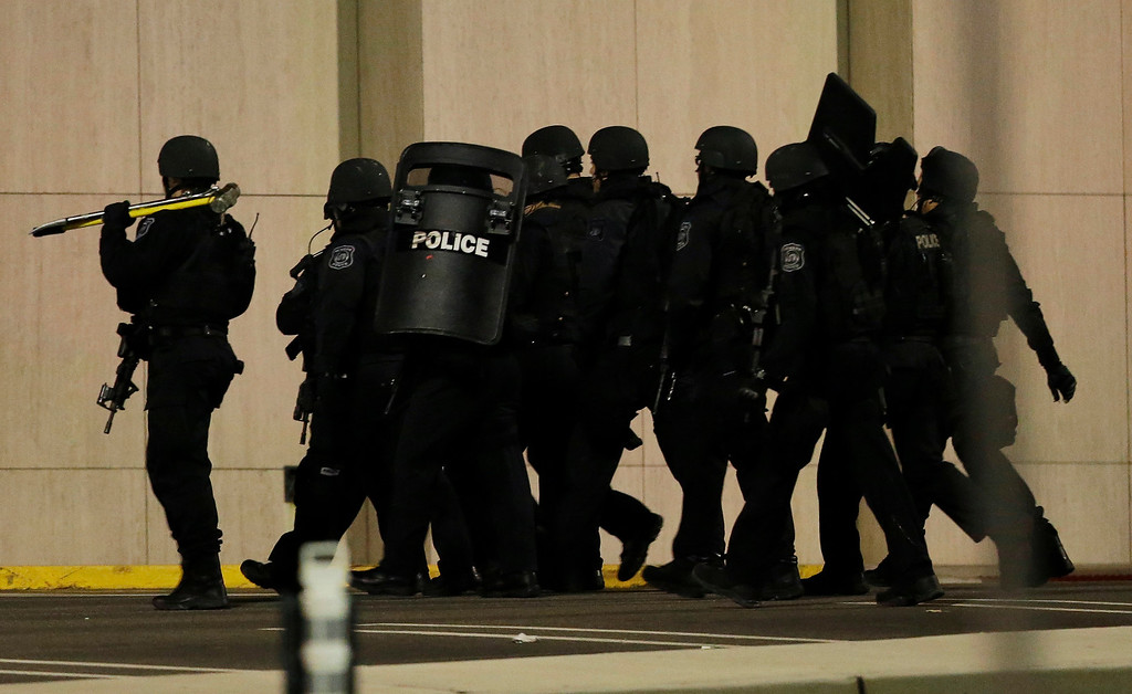 Description of . Officials wearing tactical gear walk outside of Garden State Plaza Mall following reports of a shooter, Monday, Nov. 4, 2013, in Paramus, N.J. Hundreds of law enforcement officers converged on the mall Monday night after witnesses said multiple shots were fired there. (AP Photo/Julio Cortez)