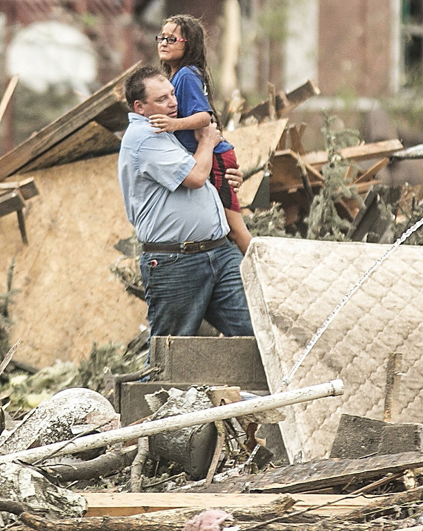 Description of . A man holds a girl after she was pulled from the basement of her destroyed home in Pilger, Neb., Monday, June 16, 2014. A hospital spokeswoman says at least one person is dead and at least 16 more are in critical condition after two massive tornadoes swept through northeast Nebraska. (AP Photo/Mark \'Storm\' Farnik)
