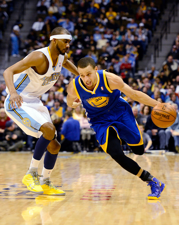 Description of . Golden State Warriors point guard Stephen Curry (30) drives past Denver Nuggets small forward Corey Brewer (13) during the second half of the Nuggets' 116-105 win at the Pepsi Center on Sunday, January 13, 2013. AAron Ontiveroz, The Denver Post