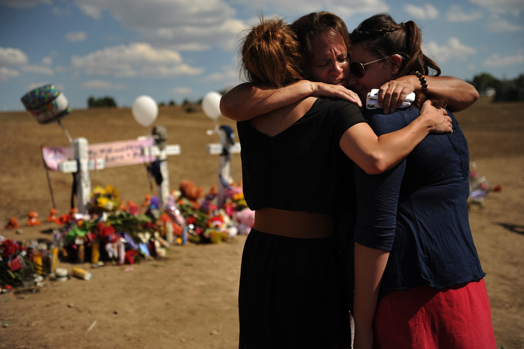 Description of . Aubrey Podschwait 19 of Parker, Julia Kouris 51 of Denver and Olivia Mancuso 20 of Parker share a healing hug while visiting the memorial for the victims of the Century 16 Theater shooting  at the corner of Sable Boulevard and Centerpoint Drive in Aurora, Colorado Monday,  July 23,  2012.      Joe Amon, The Denver Post